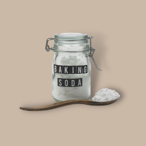 bottle of baking soda and a spoonful of baking soda against brown background