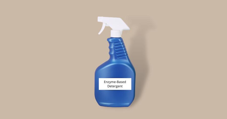 blue spray bottle of enzyme based detergent against brown background