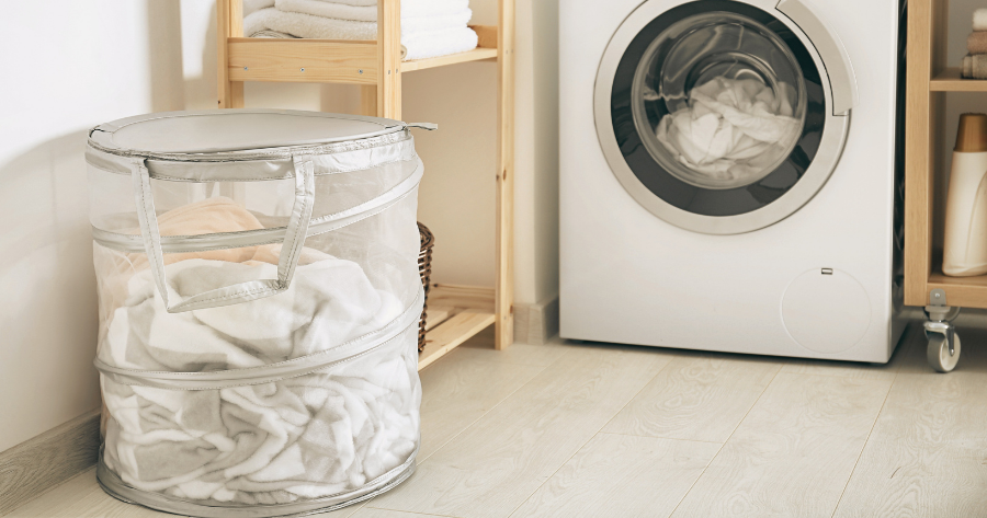 laundry hamper and clothes washer in a laundry room