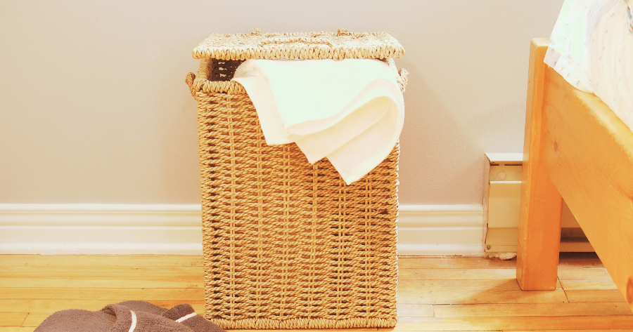 laundry hamper beside a bed