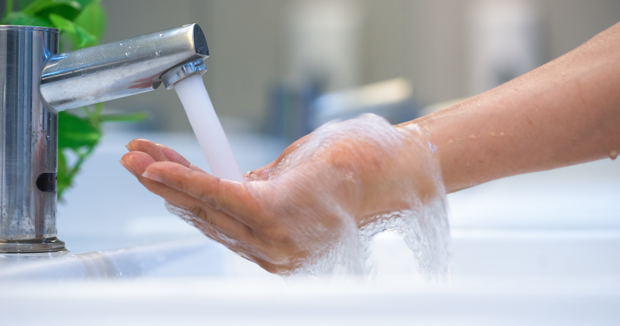 running water from a faucet to a hand