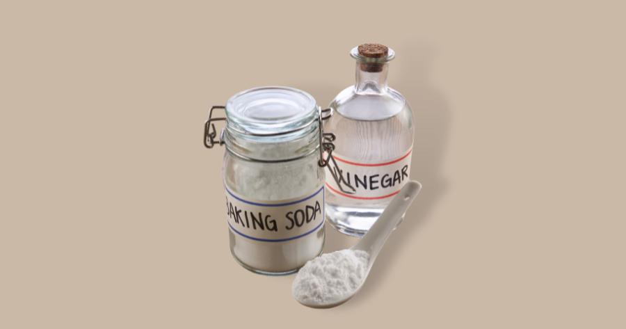 spoonful of baking soda a bottle of baking soda and a bottle of vinegar